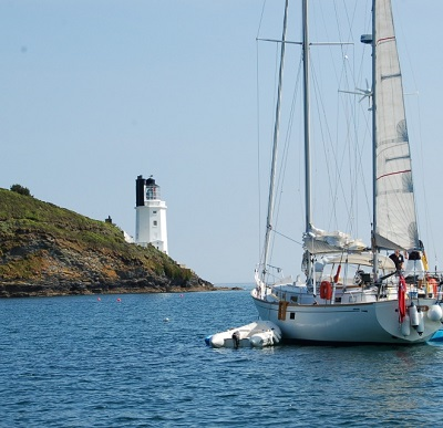 sailing yacht with lighthouse in background