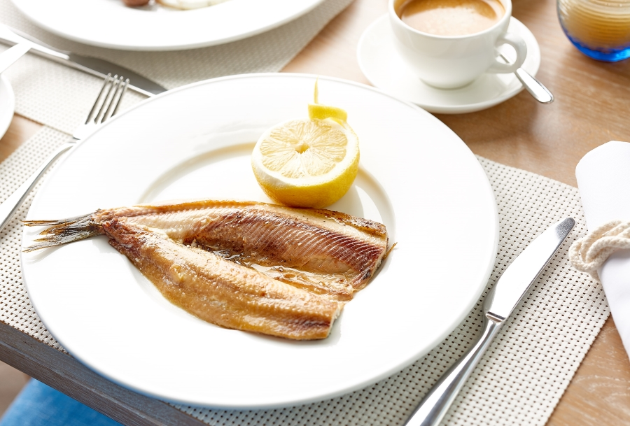 kippers and lemon on a white plate at the Idle Rocks Restaurant