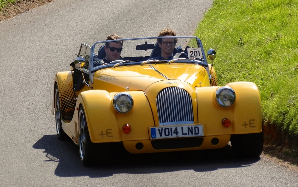 2 people driving a yellow morgan car