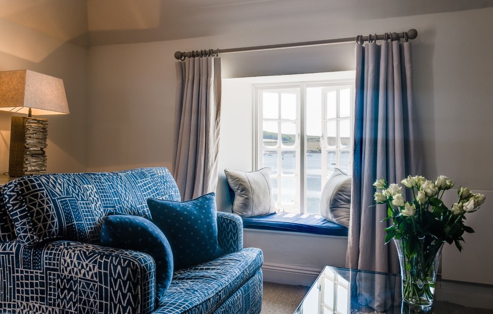 a view of the sea, from the window seat, with sofa and white roses at The Idle Rocks Hotel