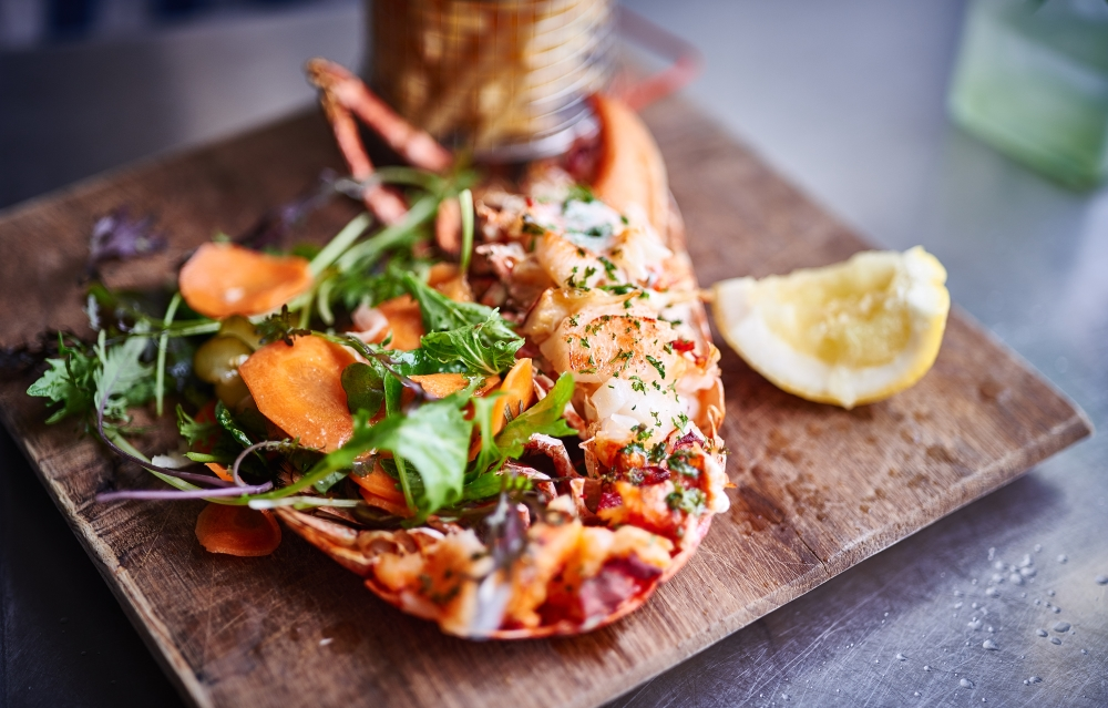 Grilled lobster on a wooden board with chips - Eat at The St Mawes Hotel