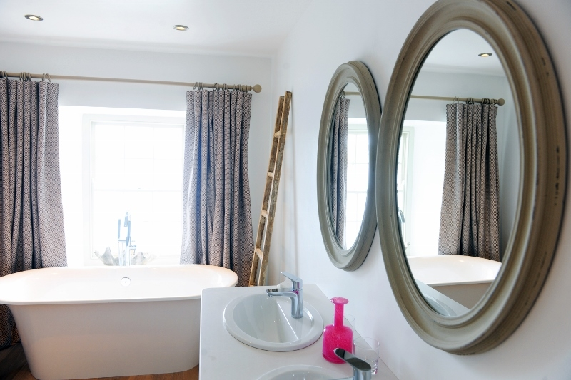 View of mirrors and freestanding bath in room 1 at the Idle Rocks Hotel