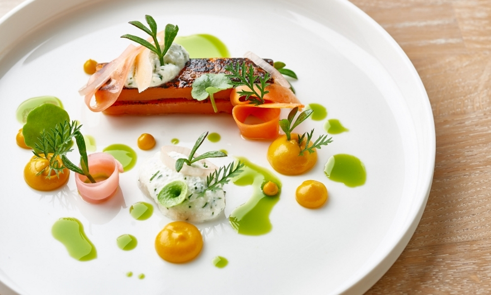 colouful green and orange carror dish on white plate